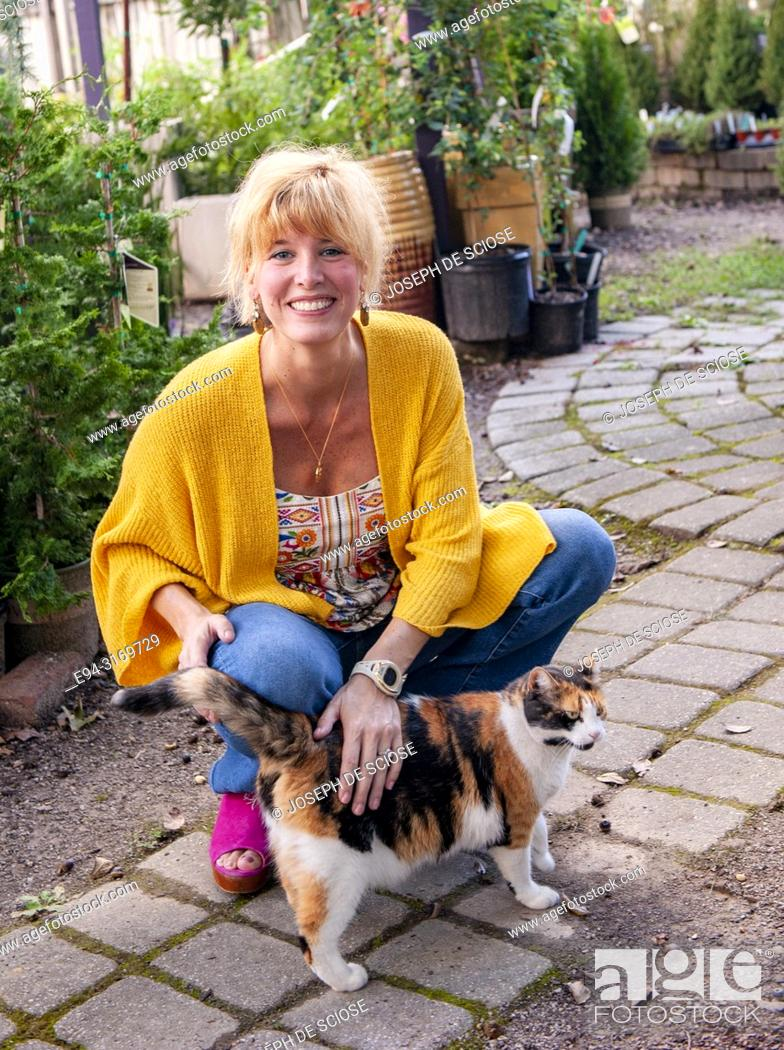 Stock Photo: A pretty 42 year old blond woman petting a cat in a garden setting.