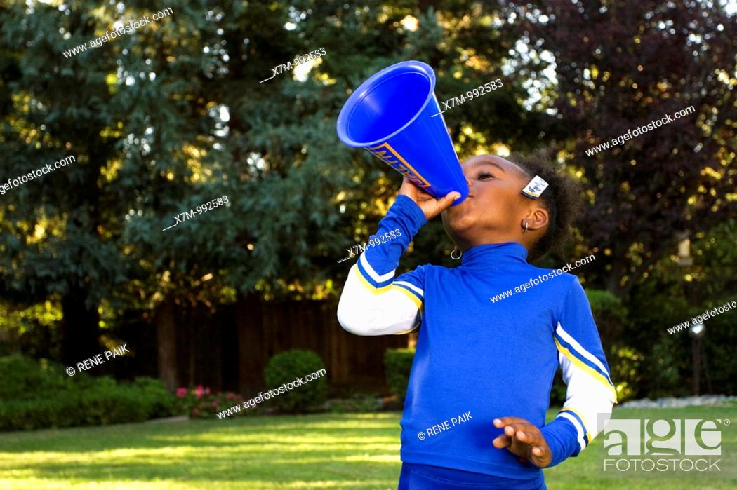 Stock Photo: A little black girl dressed as a cheerleader for Halloween yelling through a megaphone.