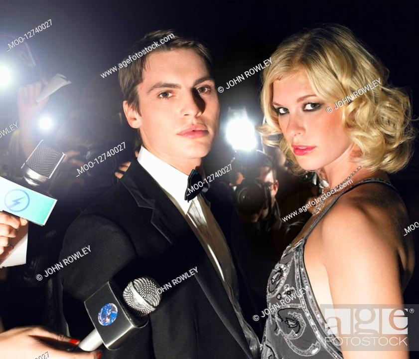 Stock Photo: Couple posing in front of paparazzi.