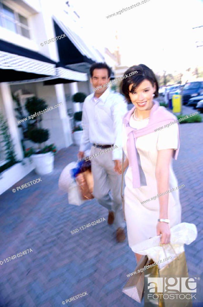 Stock Photo: Mid adult couple carrying shopping bags.