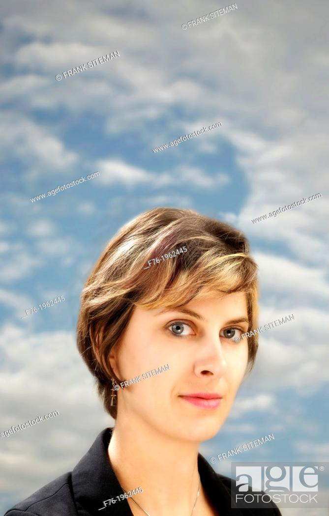 Stock Photo: Portrait of young woman with clouds in background.
