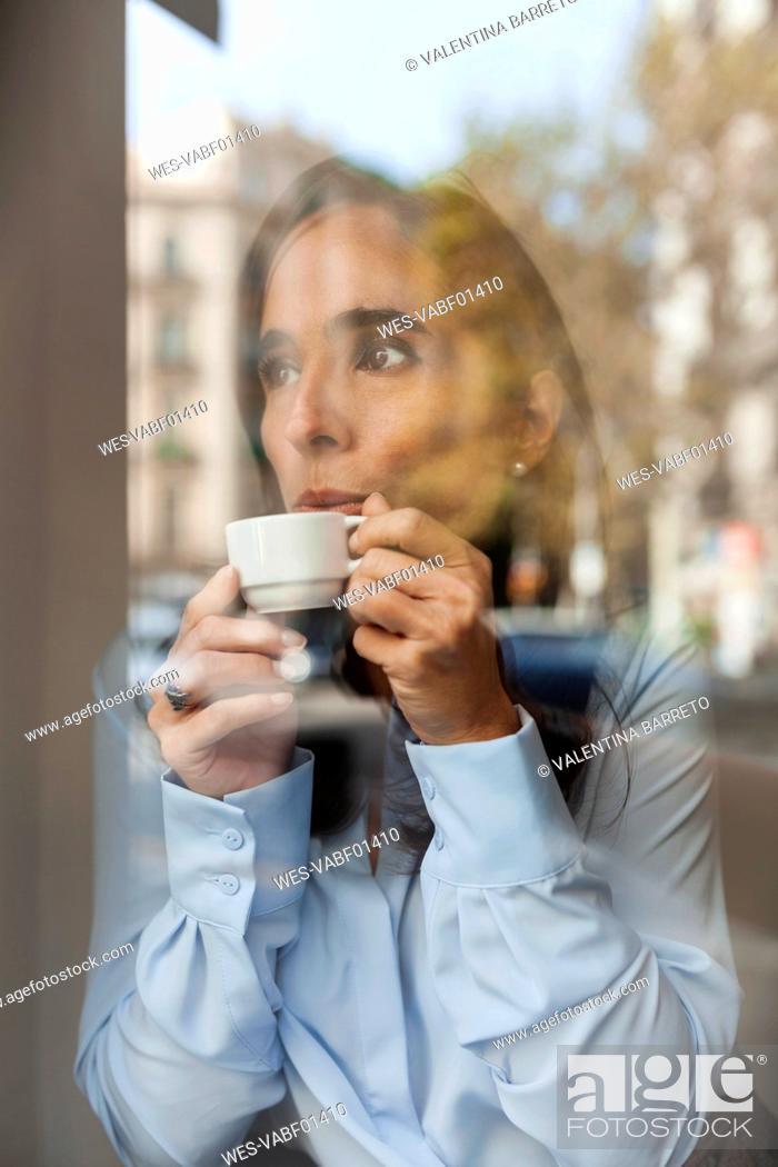 Stock Photo: Businesswoman drinking espresso behind window pane.