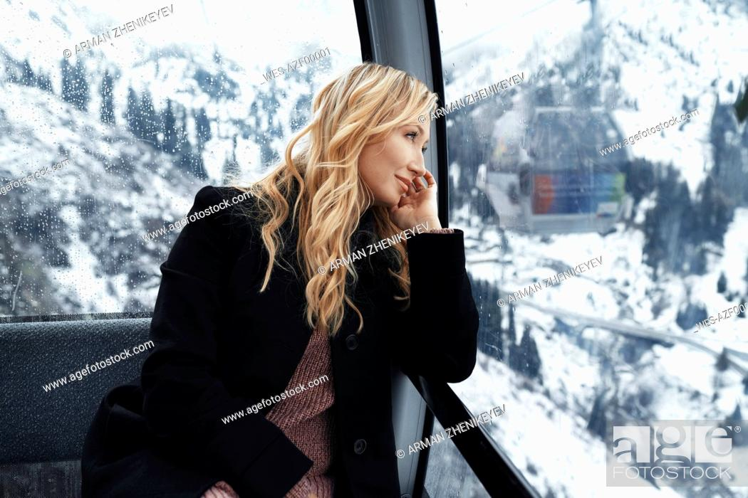 Photo de stock: Switzerland, European Alps, Woman looking out at the mountain range from the cable car gondola.
