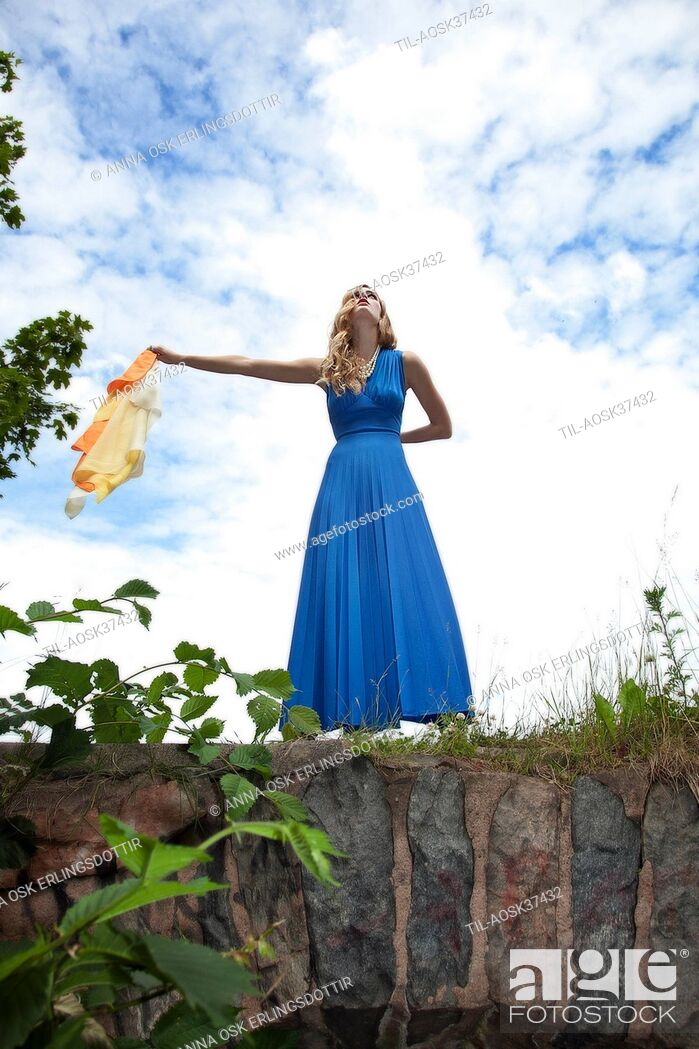 Imagen: Lone female figure wearing blue dress standing on bridge.