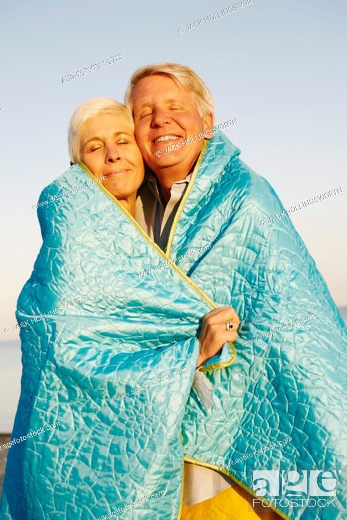 Stock Photo: Close-up of a mature couple wrapped in a blanket and smiling.