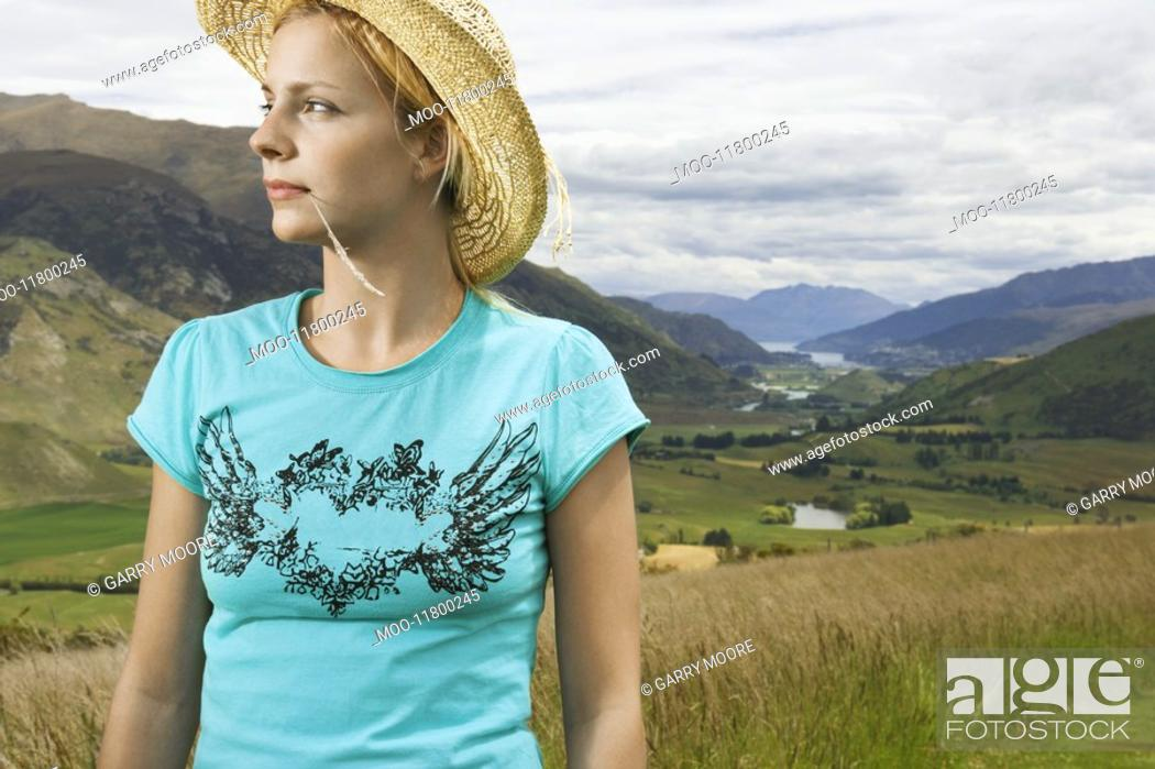 Stock Photo: Woman wearing cowboy hat in countryside.