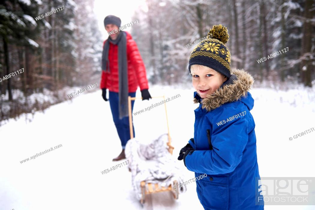 Stock Photo: Portrait of smiling little boy in winter with his father and sledge.