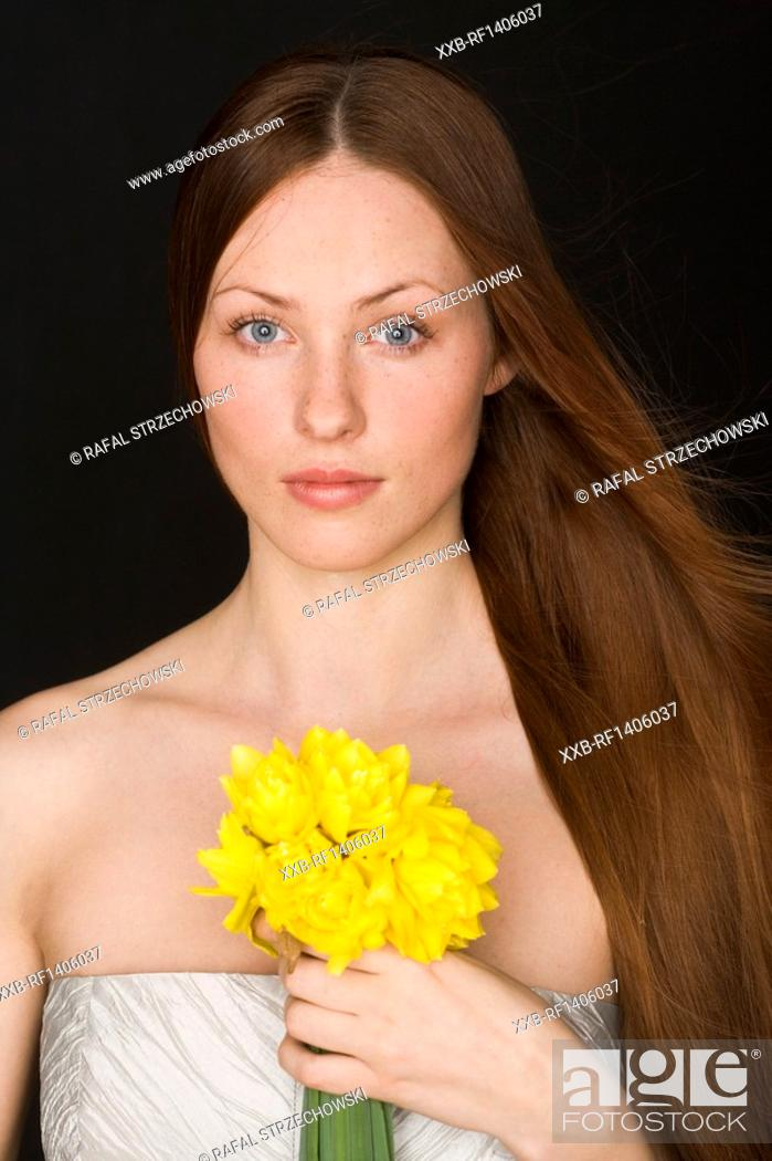 Stock Photo: young woam with banch of daffodils.