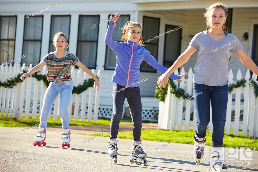 Stock Photo: Teen girls group rolling skate in the street outdoor.