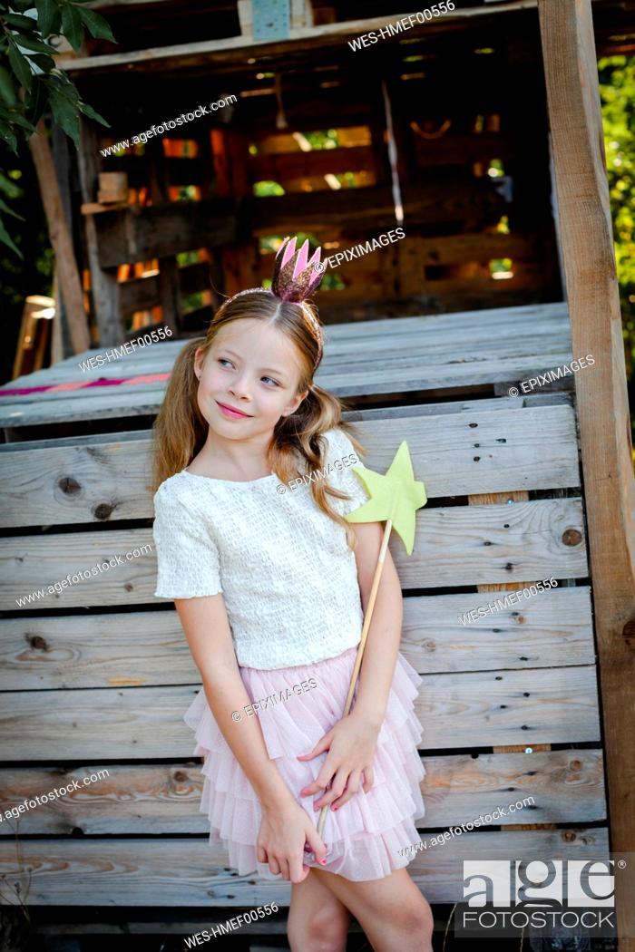 Stock Photo: Girl dressed as a princess with crown and sceptre playing in a tree house.
