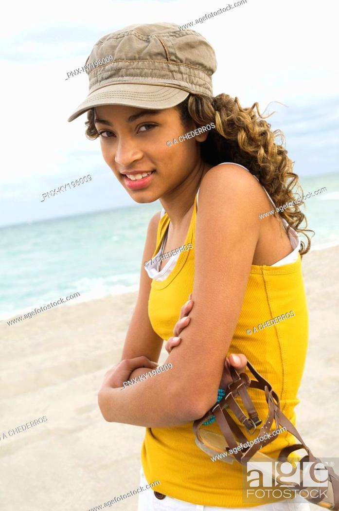 Stock Photo: Girl holding a sandal on the beach.