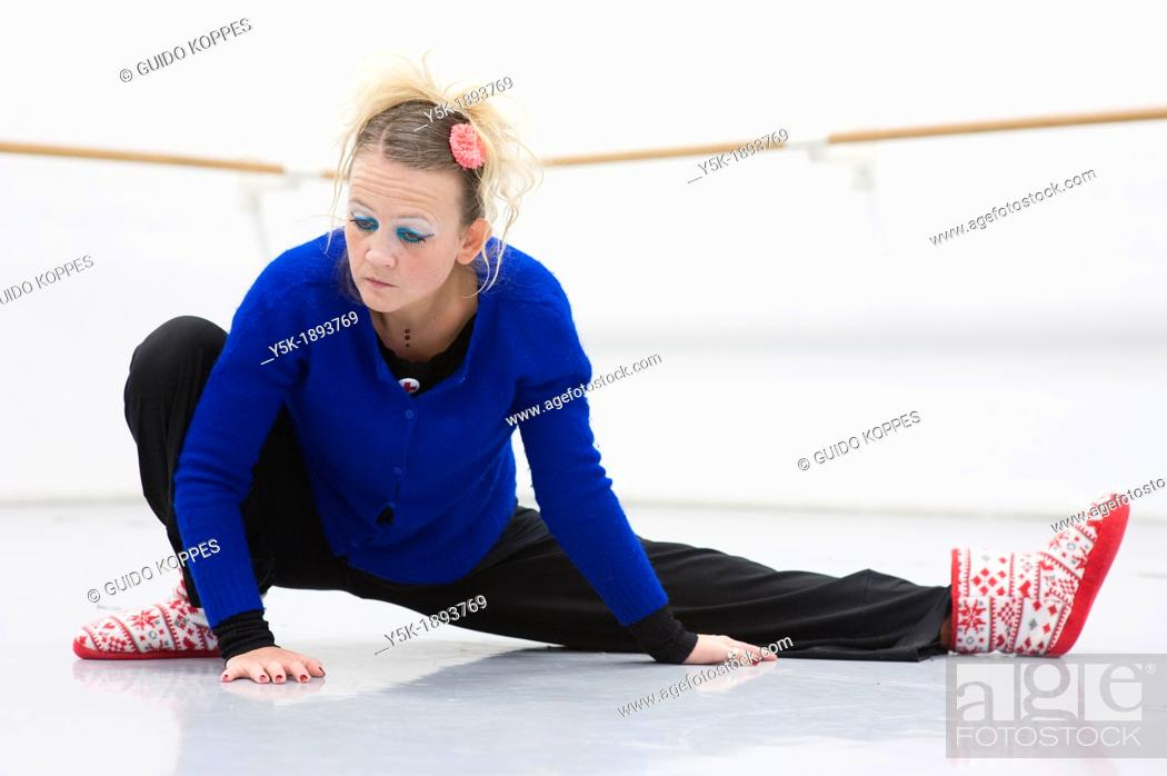 Stock Photo: Tilburg, Netherlands. A professional dancer and choreographer of modern dance busy stretching and straightening her muscles before a rehearsal of improvised.