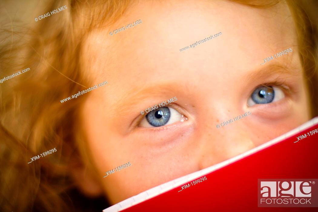 Stock Photo: Little girl, aged 5, peering over the top of her book.