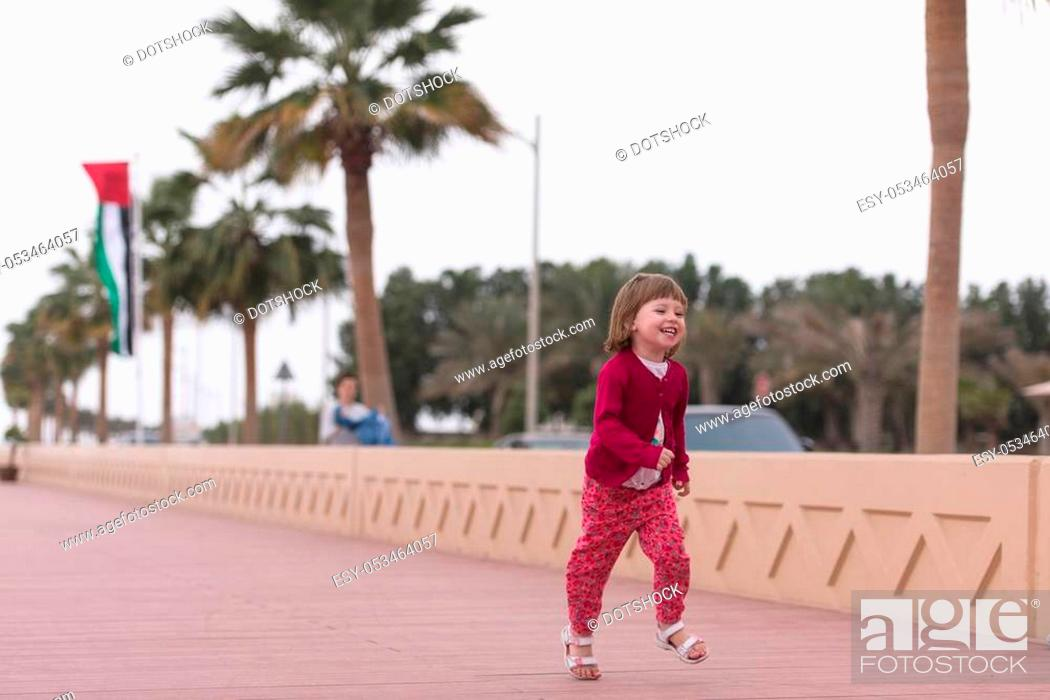 Stock Photo: cute little girl running and cheerfully spend her time on the promenade by the sea.