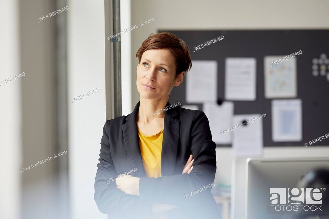 Stock Photo: Attractive businesswoman standing in office with arms crossed.