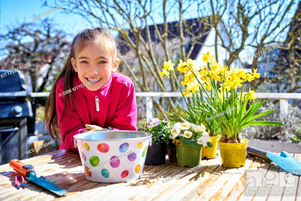 Stock Photo: portrait of happy girl planting flowers on balcony.