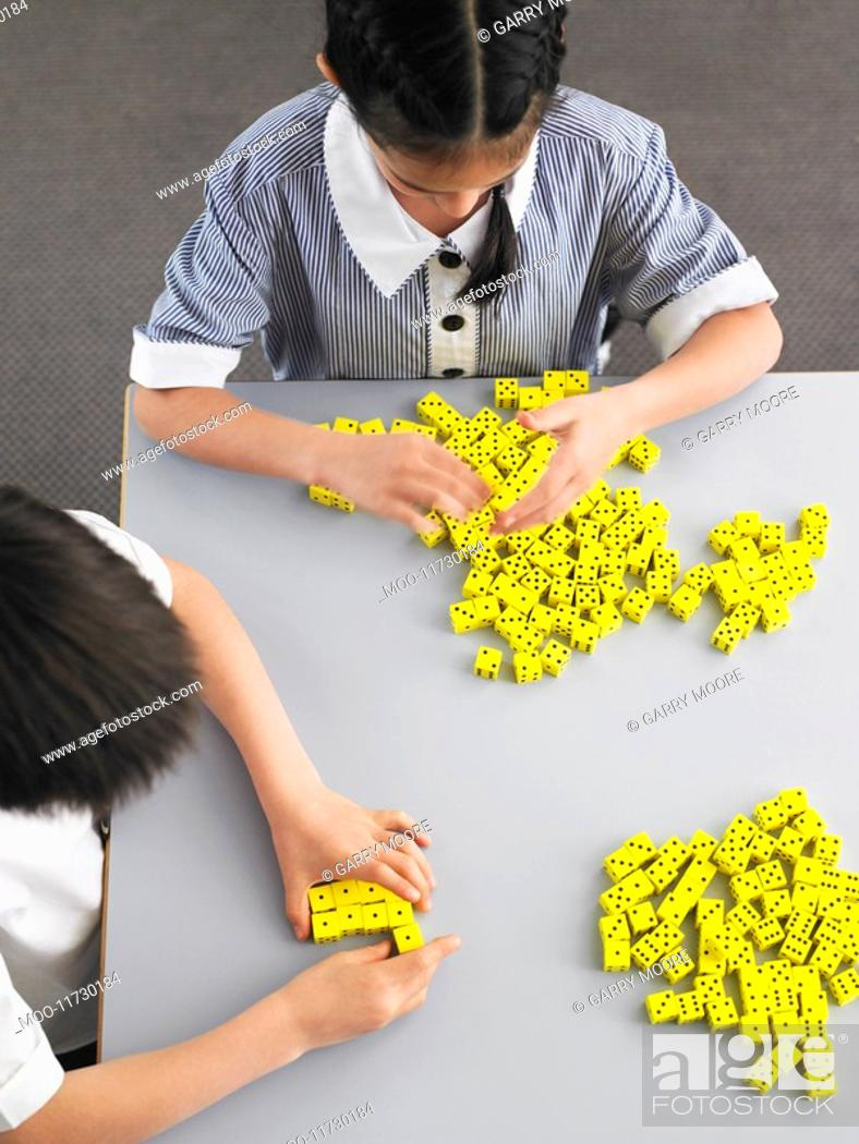 Stock Photo: Elementary students playing with dice on desk elevated view.