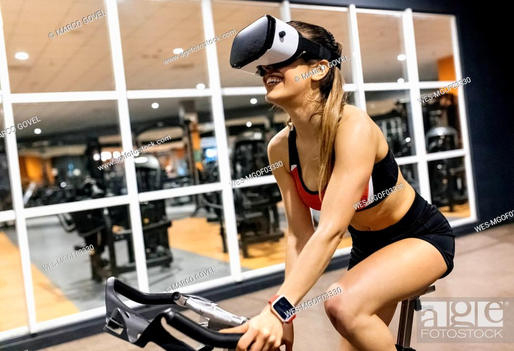 Stock Photo: Woman with VR glasses on spinning bike in the gym.