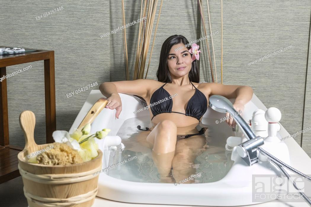 Stock Photo: Sensual young brunette in bikini lying in recreation bath enjoying massage center.