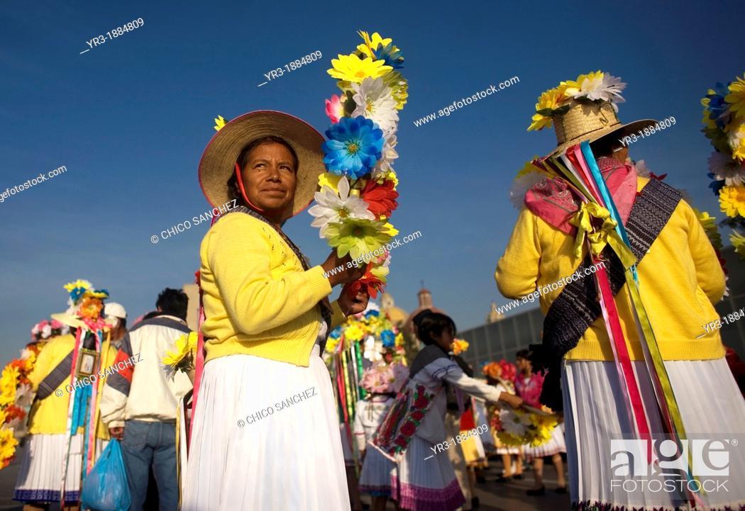 Stock Photo: An indigenous Mazahua woman from San Pedro el Alto, San Felipe del Progreso, Estado de Mexico carries a crown of flowers as part of the Danza de las Carmelitas.