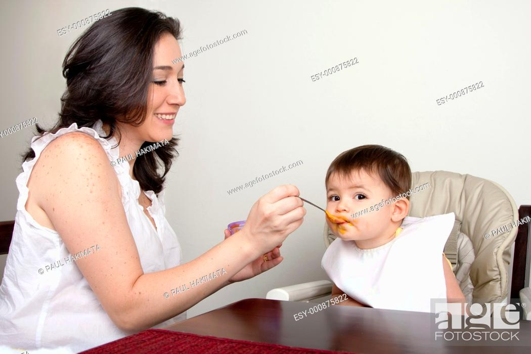Stock Photo: Beautiful happy mother or nanny feeds baby boy girl orange puree with spoon, infant eats messy, while sitting at table.