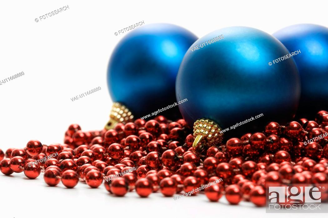 Stock Photo: Still life of large blue Christmas ornaments and strings of red beads.