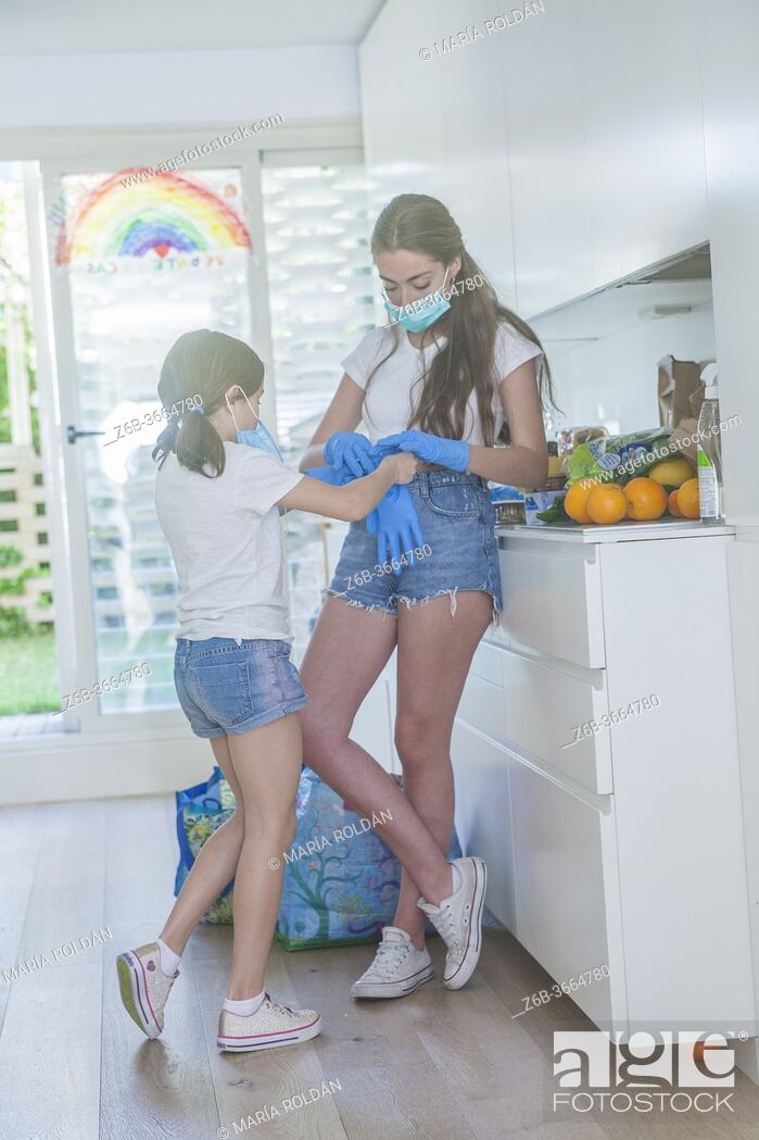 Stock Photo: 2 girls putting on gloves, they wear masks.