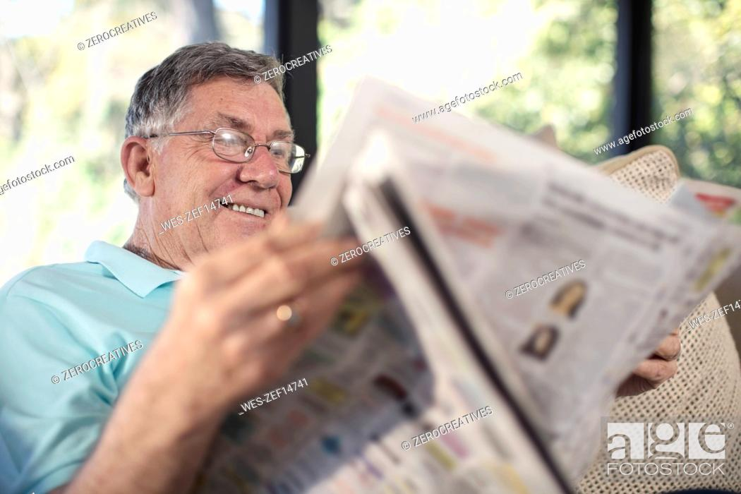 Stock Photo: Smiling senior man sitting on couch reading newspaper.