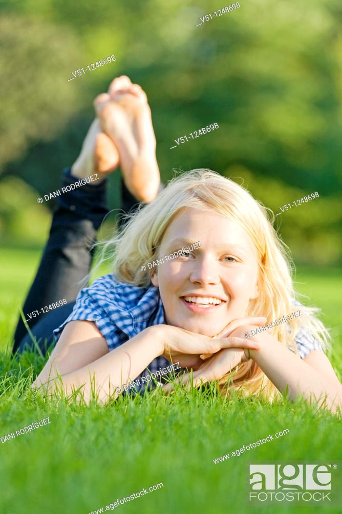 Stock Photo: Portrait a a young woman lying at the park smiling at camera.