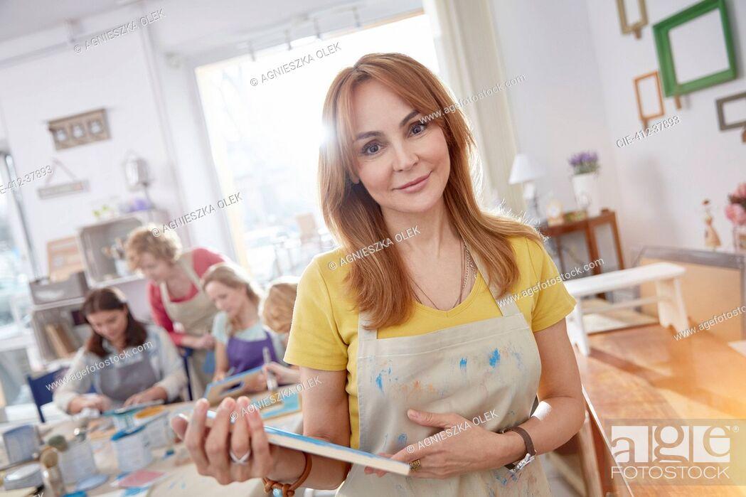 Photo de stock: Portrait confident female artist holding painted picture frame in art class workshop.