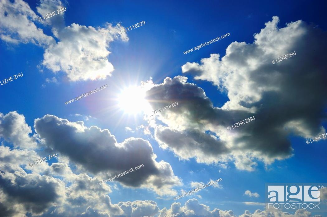 Stock Photo: cloudy blue sky with bright shiny sun.