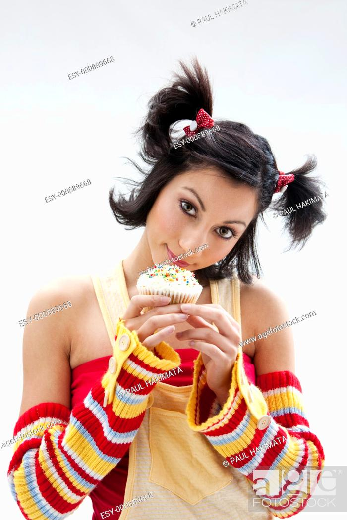 Stock Photo: Beautiful Latina girl with huge eyes open holding a cupcake, isolated.