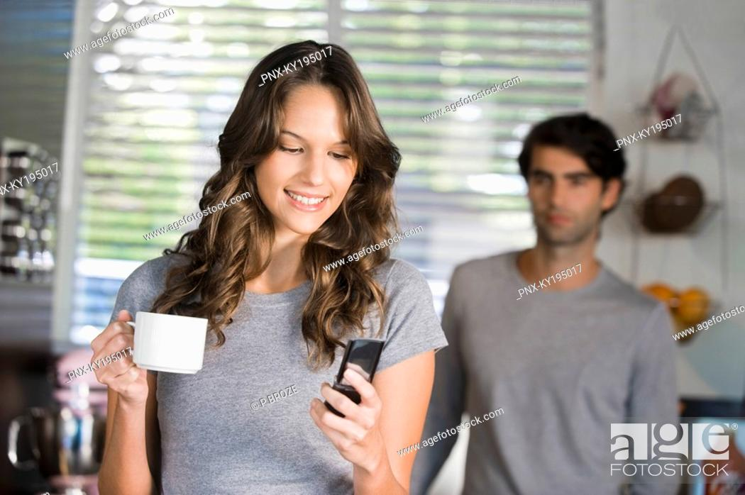 Stock Photo: Woman text messaging with a man standing in the background.