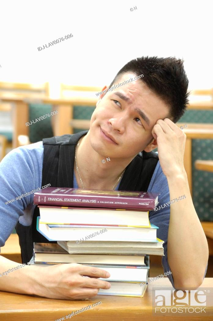 Stock Photo: Male university student thinking in a classroom.