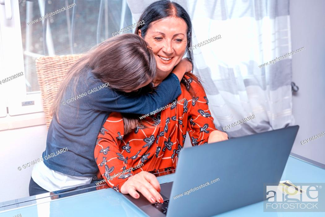 Photo de stock: Happy young girl with her mother doing online shopping, embracing her for buying something.