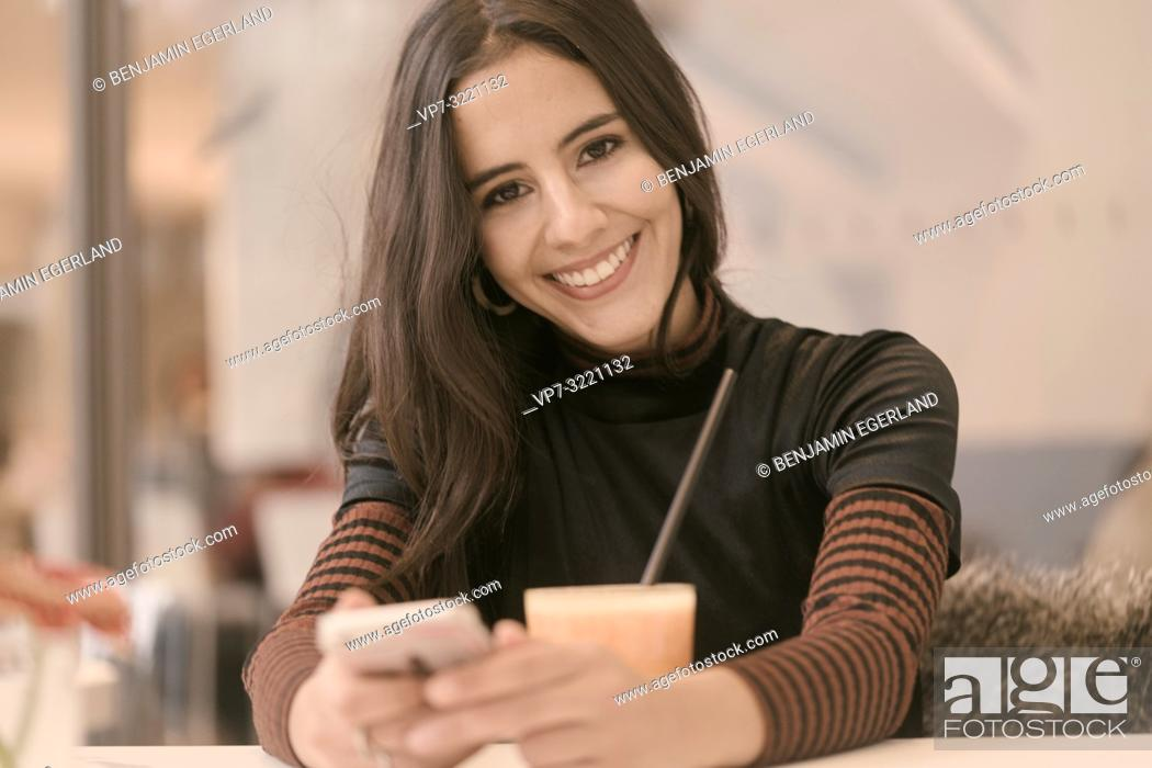 Stock Photo: portrait of happy smiling woman using phone while taking a break with healthy juice glass at table in café, in Munich, Germany.