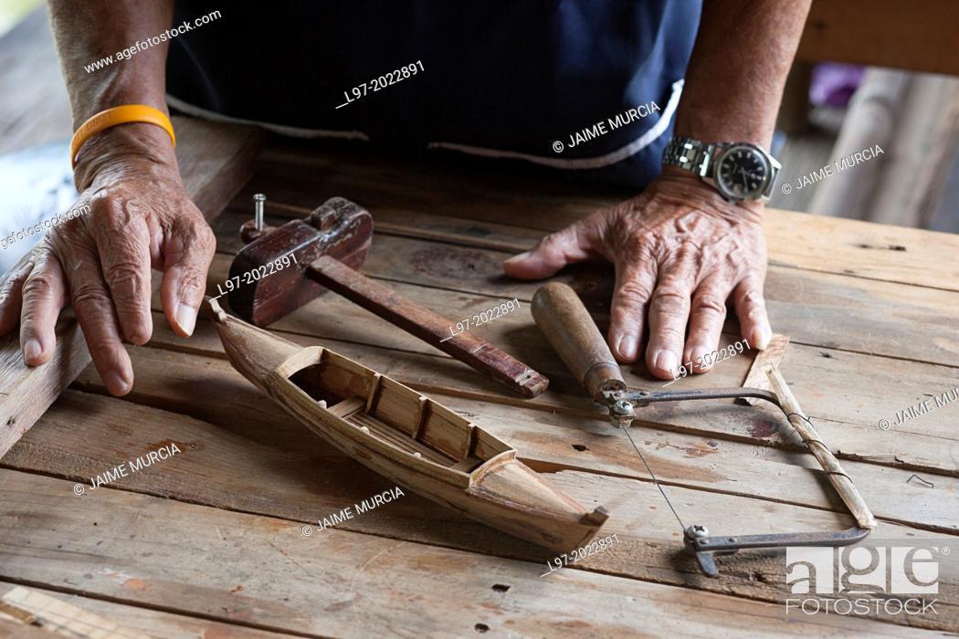 Stock Photo: Craftsmans hands with a minature traditional Thai sampan made from teak wood, Bangkok Thailand.
