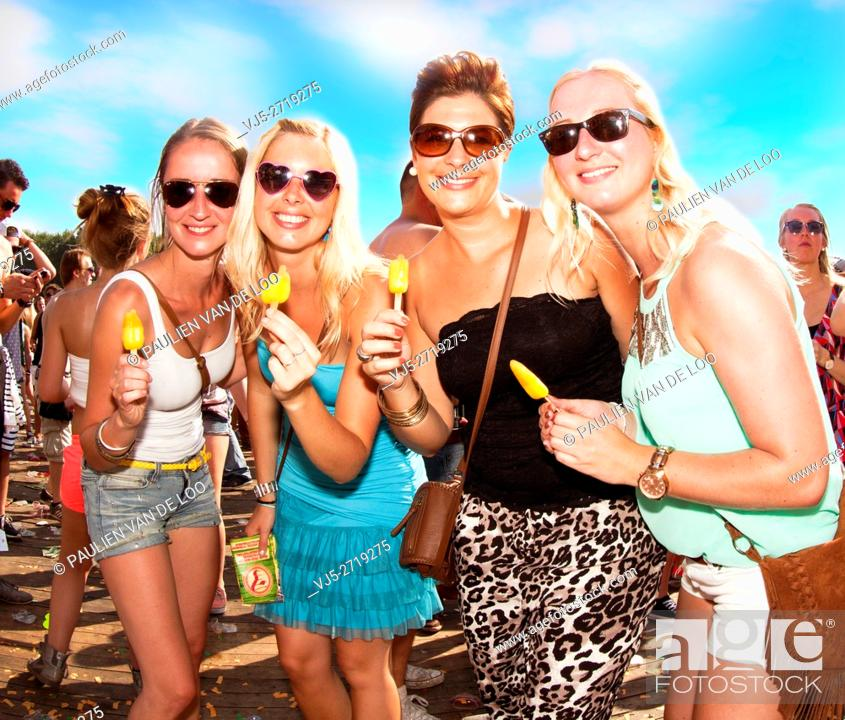 Stock Photo: Erp, Netherlands, 4 women eating an icecream while listening to the music during an event.