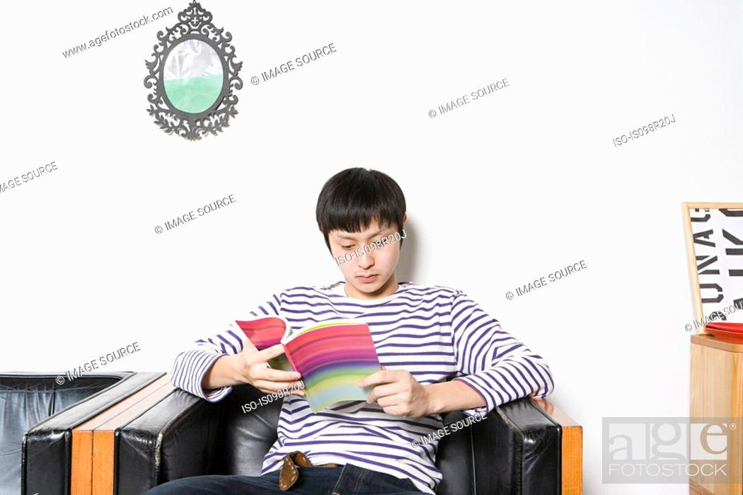 Stock Photo: Young man looking at design book.