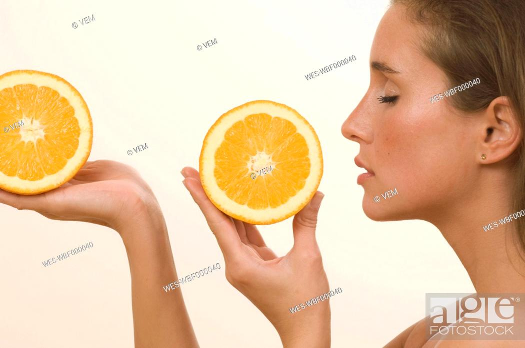 Stock Photo: Young woman holding orange slice with eyes closed.