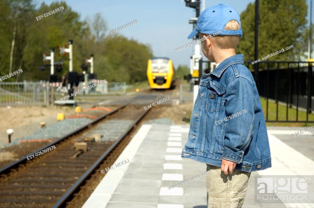 Stock Photo: Little boy waiting for the train to come on a railway station.