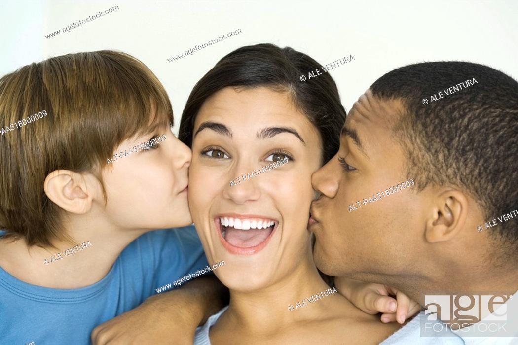 Stock Photo: Woman smiling at camera as husband and son kiss her cheeks.