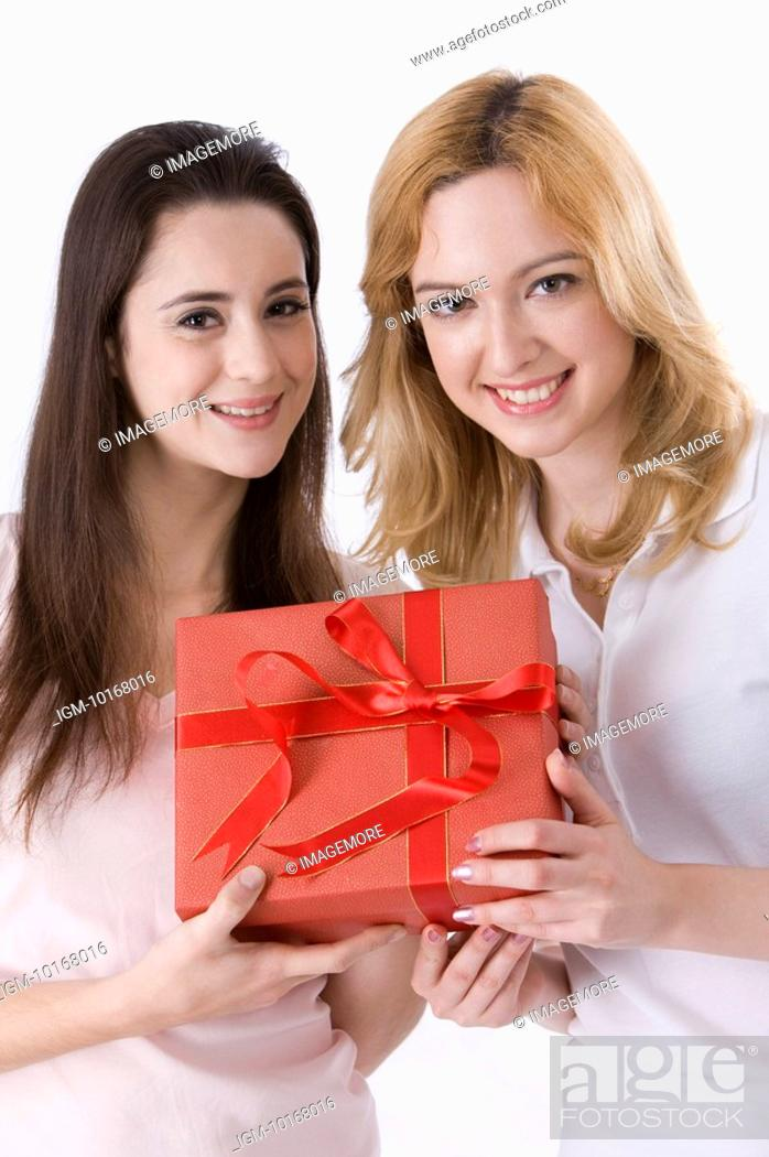 Stock Photo: Two young women holding a box of present.