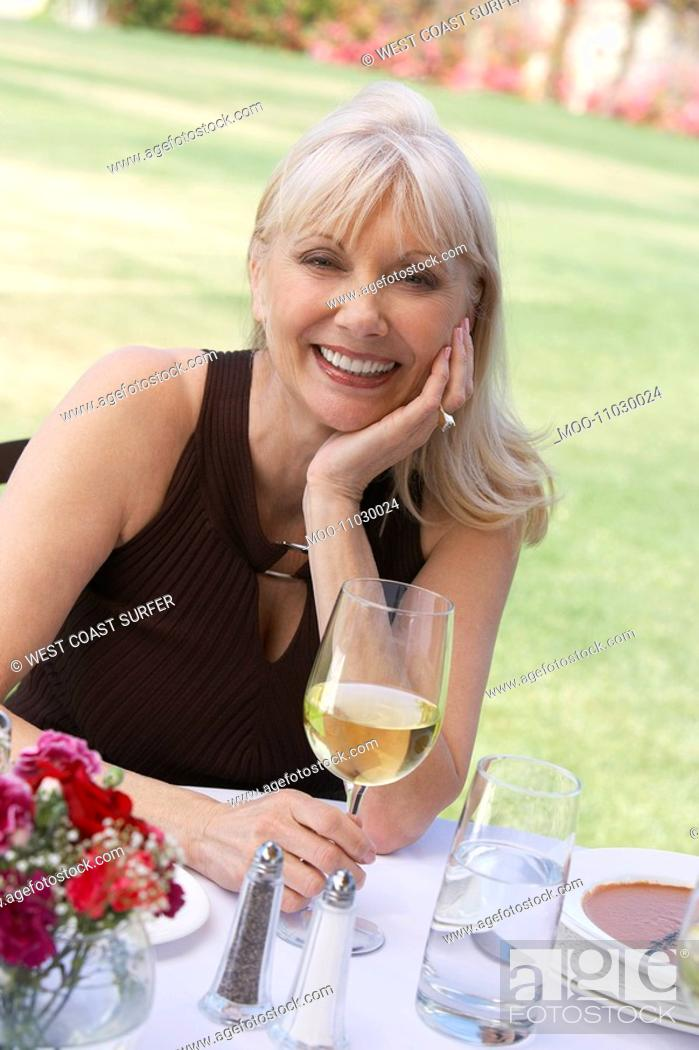 Stock Photo: Mature elegant woman sitting at table outdoors.