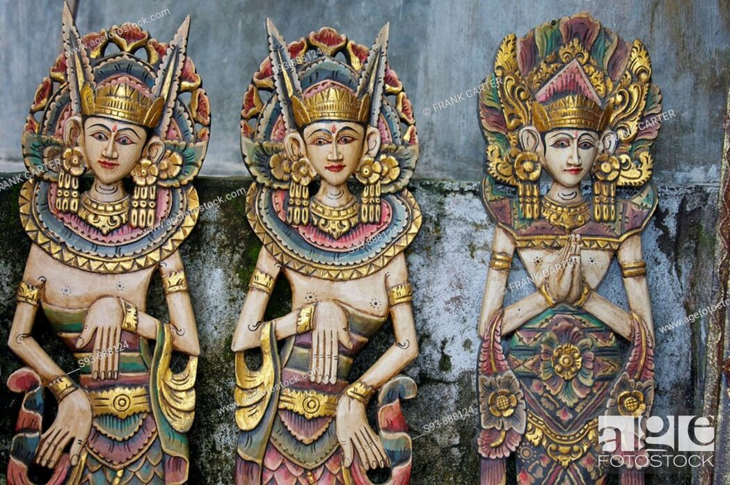 Stock Photo: Three wooden figures of Balinese dancers in traditional dress in Ubud, Bali.
