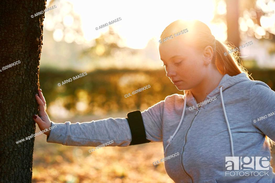 Photo de stock: Curvaceous young woman training in park, doing tree trunk push ups.