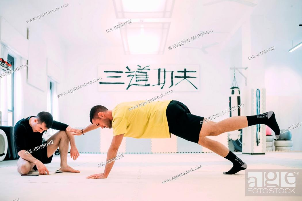 Stock Photo: Man with coach doing push ups.