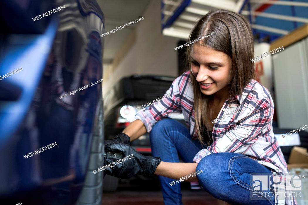 Stock Photo: Young woman wearing gloves and screwing wheel of car working in repair shop.