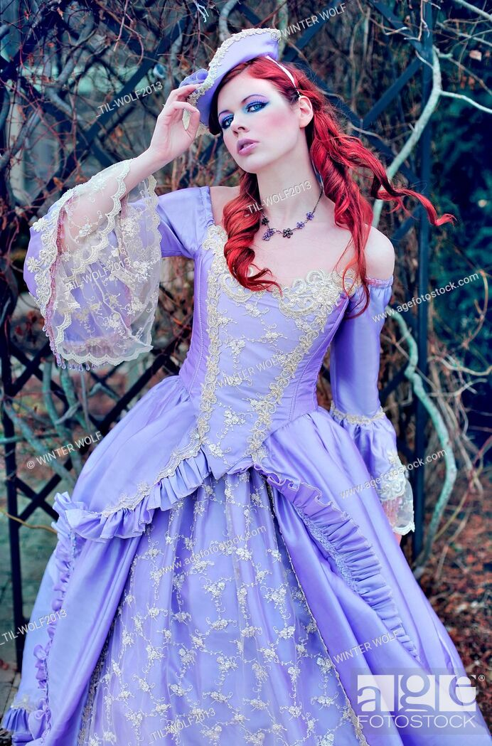Stock Photo: Pretty, sweet looking young woman with red hair wearing a fancy purple gown with lace.