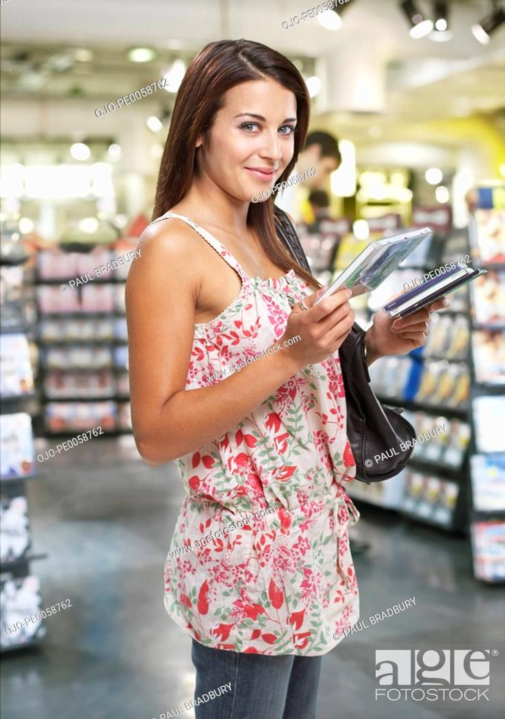 Stock Photo: Woman looking at CDs with other shoppers in background.